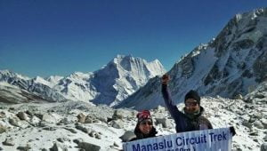 guide to manaslu circuit trek at top of larkey pass waving hand for picture