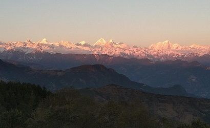 langtang Himalaya range seen under red sun during sunset from chisapani village in our chisapani nagarkot trek