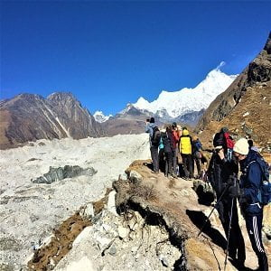 trekkers taking break by the nagzumba glacier after crossing chola pass in everest base camp gokyo trek