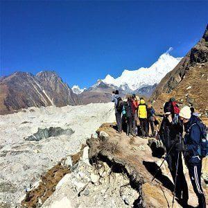 trekkers taking break by the nagzumba glacier after crossing chola pass in everest base camp gokyo trek