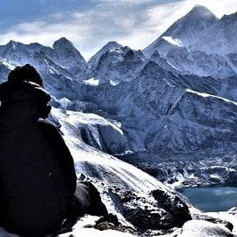 solo female trekker looking back from the last pass of her three high pass trek-gokyo lake and everest on her sight