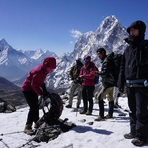 trekkers putting mini spikes to walk over chola pass after everest base camp trek - chola pass takes to gokyo ri