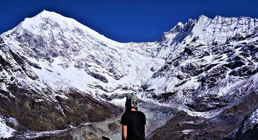 Female solo trekker looking at the glacier of Langtang himalaya