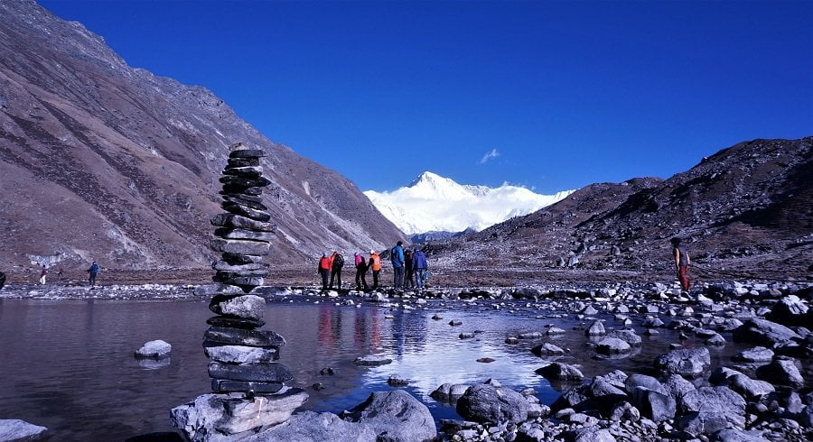 Stack of stone and trekkers on their way towards Gokyo ri in the background