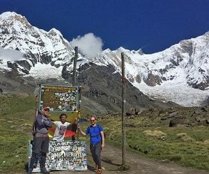 guys posing at the hording board of Annapurna base camp in their short trek to ABC