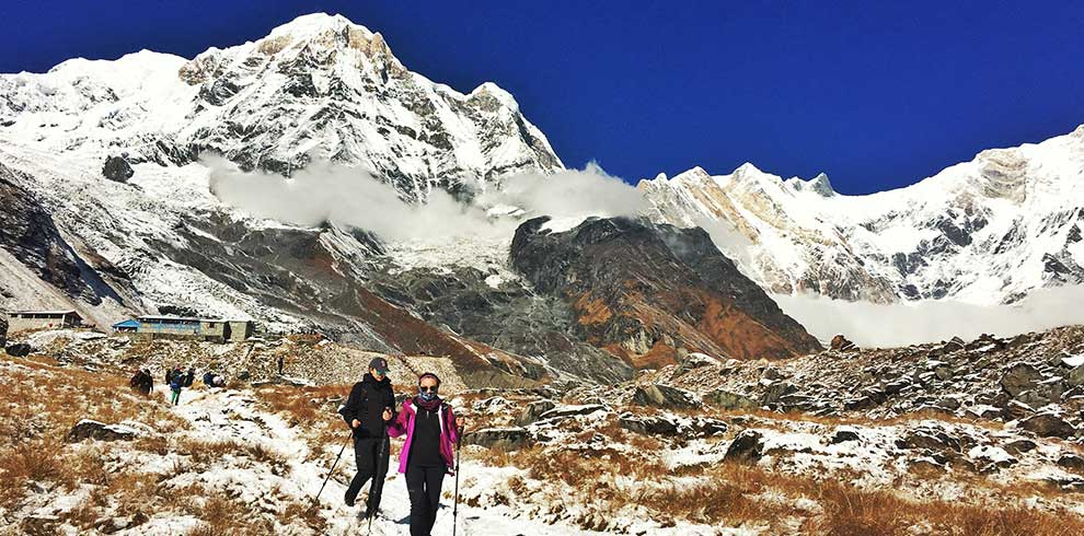 Annapurna south seen in the morning and trekkers getting down from Annapurna base camp trek