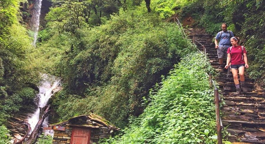 Waterfall and trekkers walking downhill in their Ghorepani Ghandruk Trekking trip in Nepal
