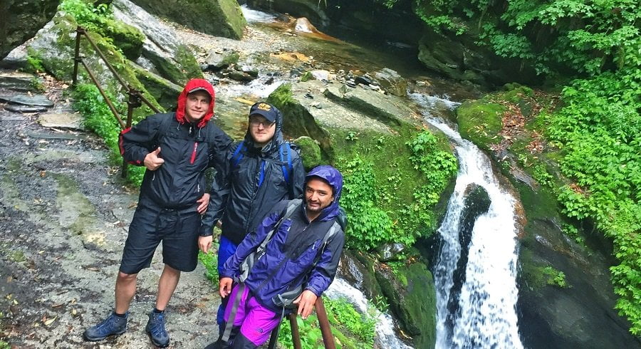Boys pose at waterfall site in the rain