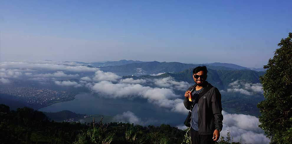 Sambit smiling at camera while the view of pokhara, lake, World peace stupa and the beautiful landscape is crystal clear in our Kathmandu Pokhara tour