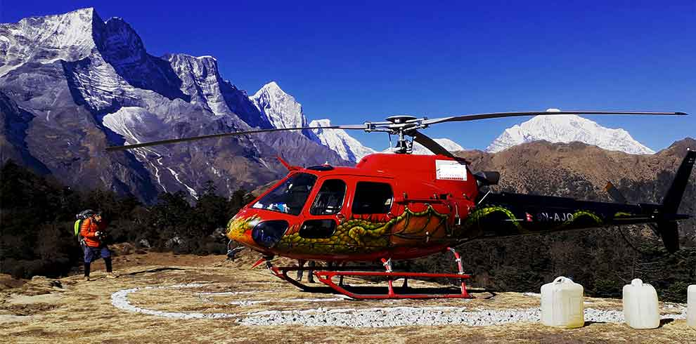 Helicopter lading infront of Everest Himalaya range while passenger are taking their breakfast