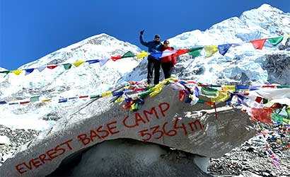 couple at everest base camp - waiving for the accomplished picture